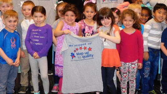 Kids holding Step up to Quality Shirt